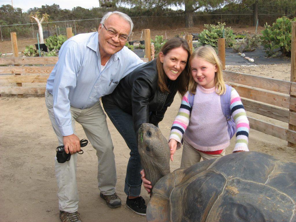 Rafael enjoying some family time while a large tortoise enjoys some fresh veggies.